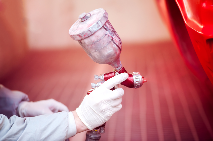Worker painting a red car in paiting booth using professional tools and spray gun