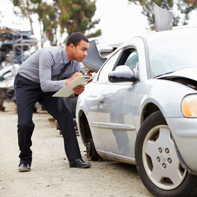 Loss Adjuster Crouching Down Inspecting Car Involved In Accident.