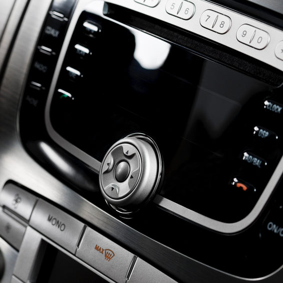 Modern car (Ford Mondeo 2009) audio system with 6 compact disc changer and mobile phone control in a car. There is climate control system below audio system.